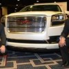 Two Hispanic Faces Behind GMC Trucks